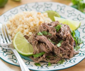 A Cup Of Shredded Indian Spiced Beef With Cauliflower Rice, Lime Wedges, Cilantro, And a Fork