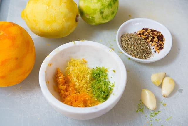 Citrus Chicken Rub - Orange Zest, Lemon Zest, and Lime Zest In White Marble Pinch Bowl with Peeled Garlic Cloves, Dried Oregano, and Red Pepper Flakes