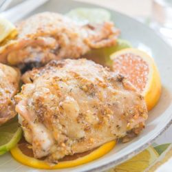 Citrus Garlic Herb Chicken Thighs With Fresh Lemon, Cara Cara Orange, and Lime Wedges On Plate