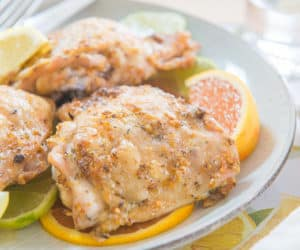 Citrus Garlic Herb Rubbed Chicken Thighs On Plate And Fresh Citrus Wedges
