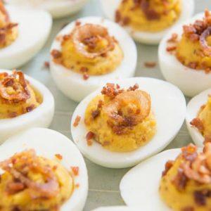 Bacon and Crispy Shallot Deviled Eggs On Light Gray Plate