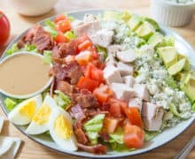 Rows of Cobb Salad Ingredients on a Plate with Dressing Ramekin