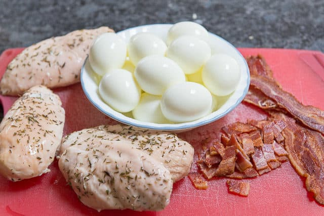 Crockpot Chicken Breast, Hardboiled Eggs, And Roasted Bacon On Red Cutting Board