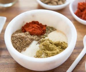 Ground Annatto, Ground Coriander, Ground Cumin, Dried Oregano, Garlic Powder, Onion Powder In Marble Bowl For Homemade Sazon Mix