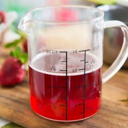 Strawberry Syrup In Glass Measuring Cup on Cutting Board