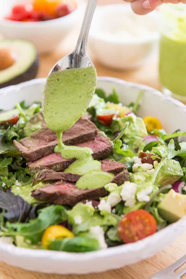 Drizzling Cilantro Lime Dressing Over Mexican Steak Salad