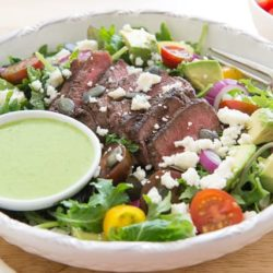 Steak Salad In Low Bowl with Sliced Steak, Cilantro Dressing, Queso Fresco, Avocado, Tomato