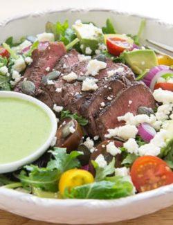 Steak Salad In Low Bowl with Sliced Steak, Cilantro Dressing, Queso Fresco, Avocado, Tomato