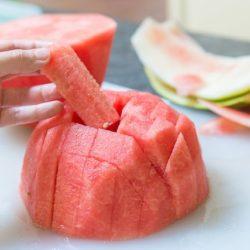 A close up of watermelon sticks on a cutting board