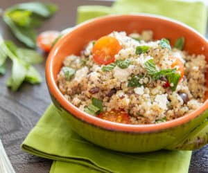 Mediterranean Quinoa Salad in Green bowl with Feta, Olives, and Mint