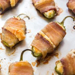 Bacon Wrapped Jalapeños On a Sheet Pan with Cheese Oozing Out