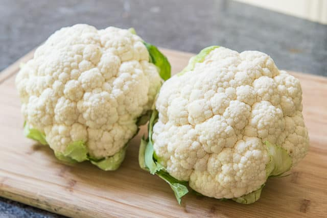 Two Heads of Cauliflower On Wooden Board
