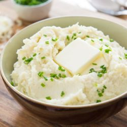 Cauliflower Mashed Potatoes In a Brown Bowl with Chives and Pat of Butter On Top