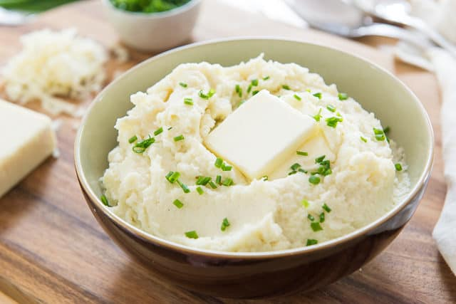 Mashed Cauliflower - In a Brown Bowl with Chives and Pat of Butter On Top