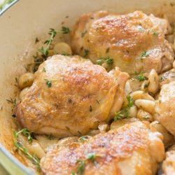 40 Clove Garlic Chicken Served in a Green Braiser Dish with Thyme Sprigs