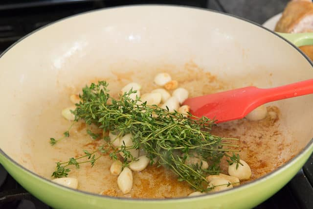 Garlic Cloves and Thyme Sprigs Cooking in Green Braiser Dish