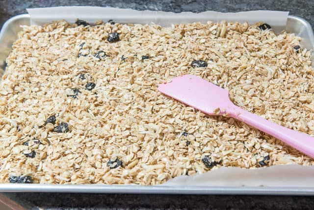 Spreading the Homemade Granola Mixture on Parchment Sheet Pan