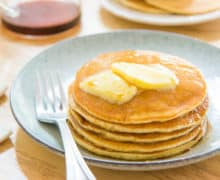 Buttermilk Pancakes Plated in a Stack on a Blue Plate with Butter Pats and Syrup On Top