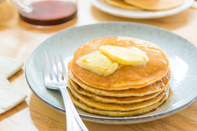 Buttermilk Pancakes - Plated in a Stack on a Blue Plate with Butter Pats and Syrup On Top