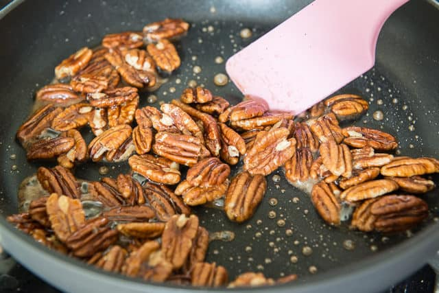 Stirring maple candied pecans In Nonstick Skillet with Spatula
