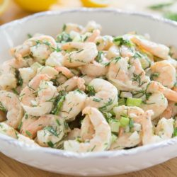 A big white low bowl filled with shrimp salad studded with celery and dill