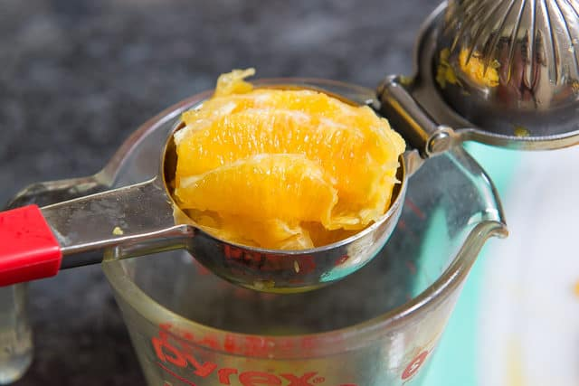 Squeezing Fresh Cut Orange in Handheld Squeezer