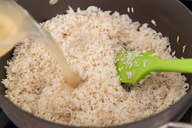 Pouring Chicken Stock Into the Rice Pilaf Recipe Batch
