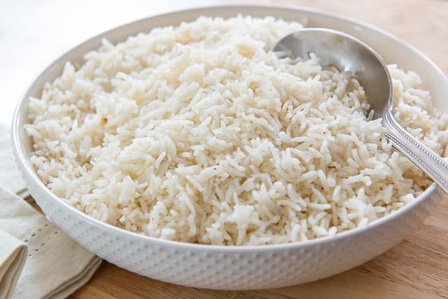 One Batch of Rice Pilaf Recipe in White Bowl with Serving Spoon