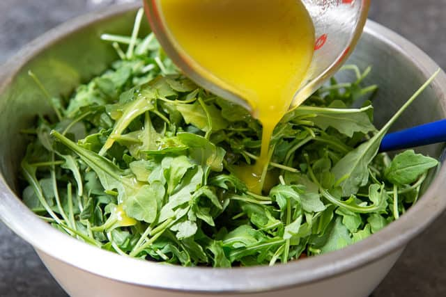 Pouring Lemon Vinaigrette Over Arugula