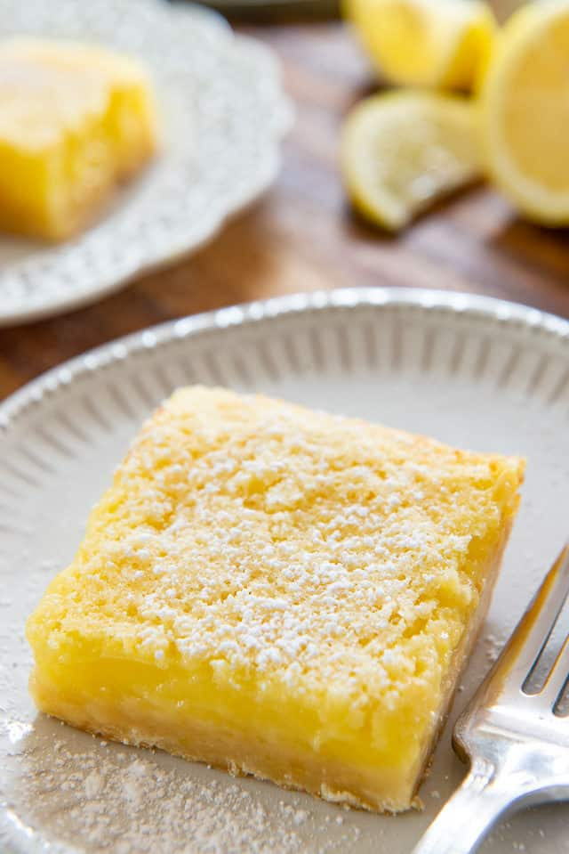 Lemon Bars - On White Plates with Fork and Powdered Sugar Dusting