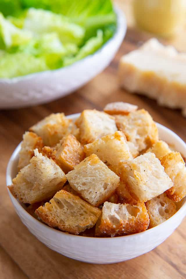 Homemade Croutons - In a White bowl on Wooden Board