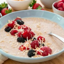 Overnight Oats in a blue Bowl Sprinkled with Fresh Berries and Coconut