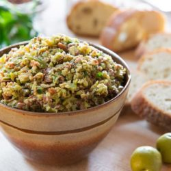 Tapenade In a Brown Bowl with Bread Slices and Olives