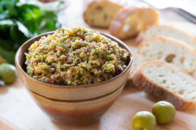 Olive Tapenade - In a Brown Bowl with Baguette Slices in Background