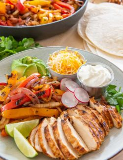Chicken Fajitas - On a Plate with Cheese, Sour Cream, and Lime Wedges
