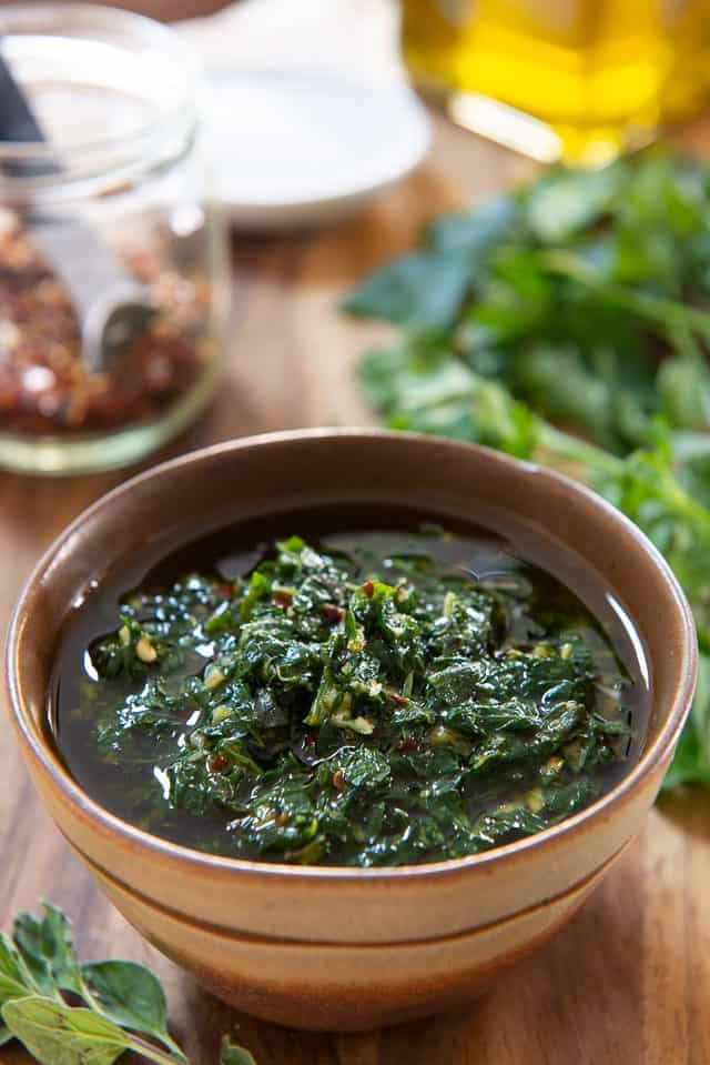 Chimichurri - In a brown Bowl with Herbs and Pepper Flakes on Wooden Board