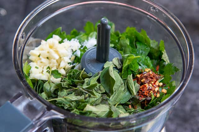 Herbs, Garlic, and Pepper Flakes in Food Processor Bowl