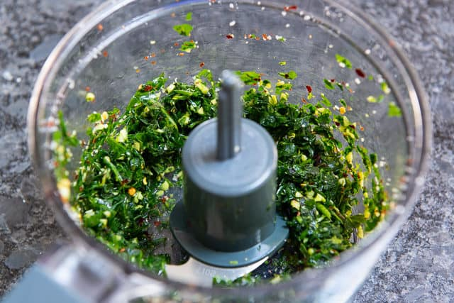 Ground Up Herbs, Garlic, and Pepper Flakes in Food Processor Bowl