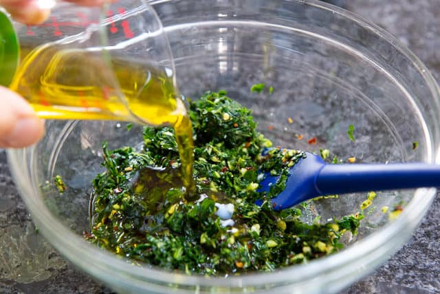 Adding Olive Oil to Ground Up Herbs, Garlic, and Pepper Flakes in Bowl