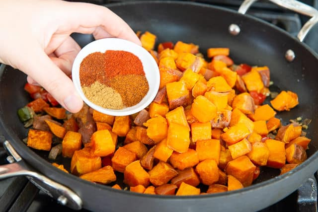 Adding Spices to Roasted Sweet Potato Cubes in Skillet