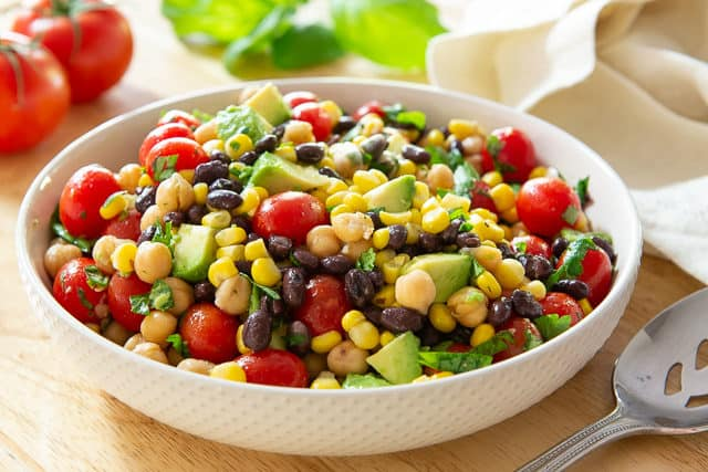 Black Bean Corn Avocado Salad with Tomatoes and Chickpeas in White Dish