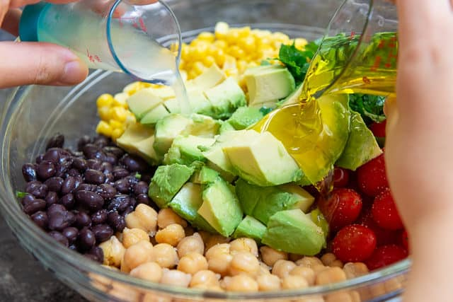 Adding Lemon Juice to Black Bean Corn and Avocado Mixture in Bowl