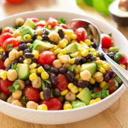 Avocado Bean Salad In White Bowl with Corn and Tomatoes and Spoon