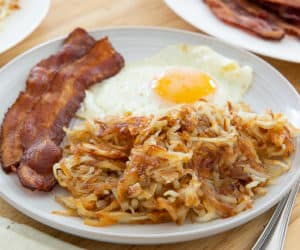 Hash Browns On a Plate With Egg and Oven Bacon