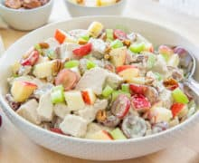 Waldorf Chicken Salad In a White Bowl With Grapes, Pecans, Apples, Celery, and a Mayonnaise Dressing
