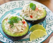 Crab Stuffed Avocado Served on Blue Plate with Lime Wedges