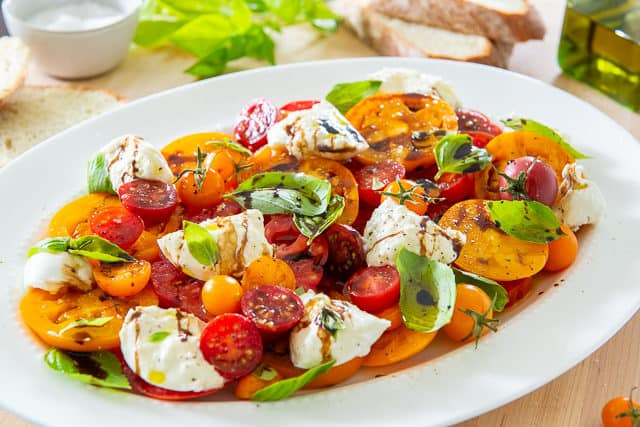 Burrata Salad - On White Platter With Heirloom Tomatoes, Fresh Basil, Balsamic