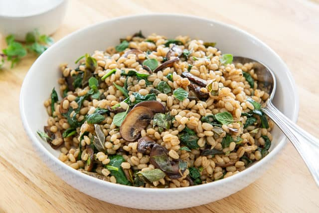 Mushroom Barley Side Dish in White Bowl with Spinach and Herbs