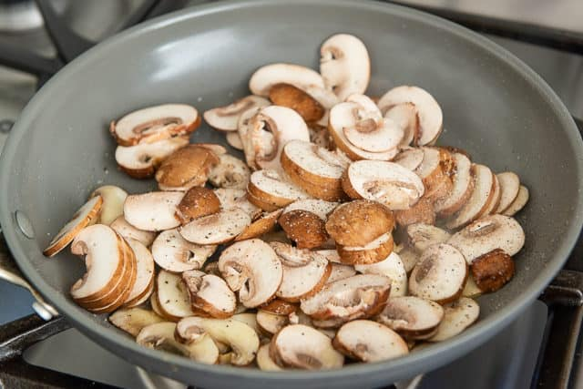 Sliced Baby Bella Mushrooms Browning in a Ceramic Skillet