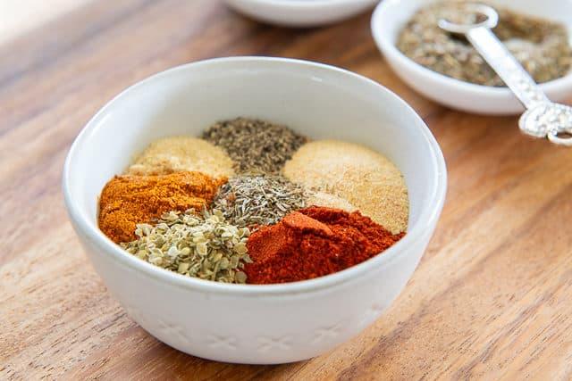 Cajun Seasoning Recipe - Spoonfuls of Paprika, Garlic Powder, Onion Powder, Thyme, Oregano, Cayenne Pepper in White Bowl